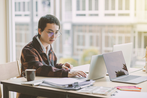 Young Man Working On His Laptop And Computer In The Office Stock Photo -  Download Image Now - iStock