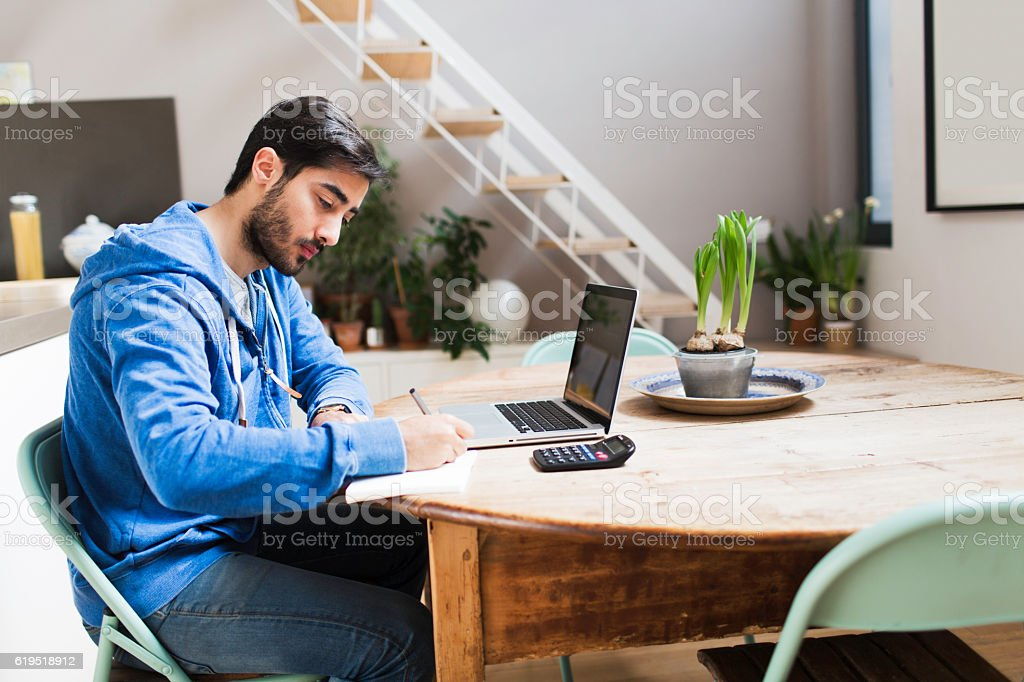 Young man working on his laptop at home. stock photo