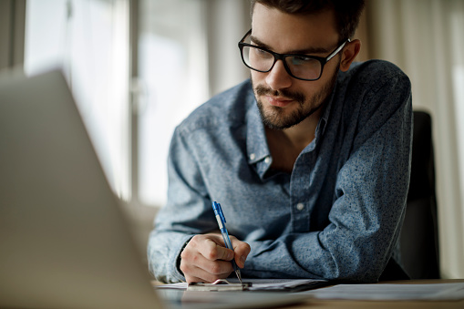 istock Young man working on laptop and taking notes 1135300996