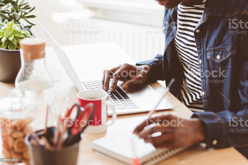 Young man working on laptop and taking notes stock photo