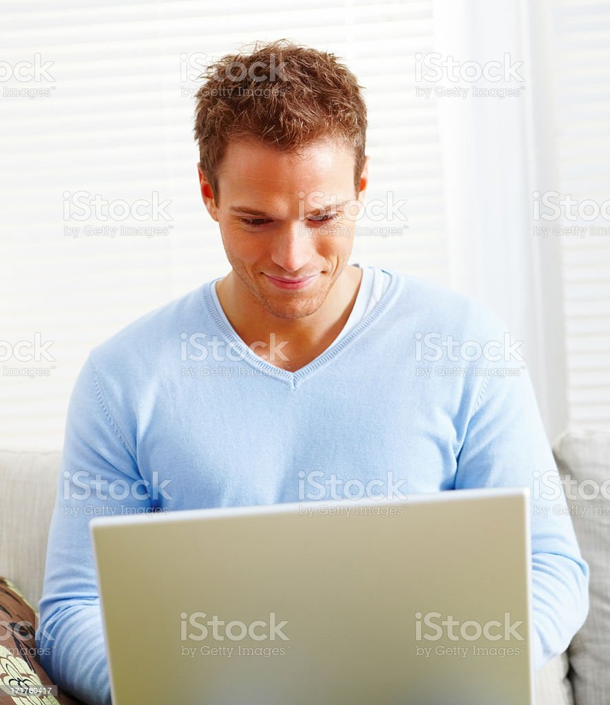 Young man working on laptop computer at home stock photo