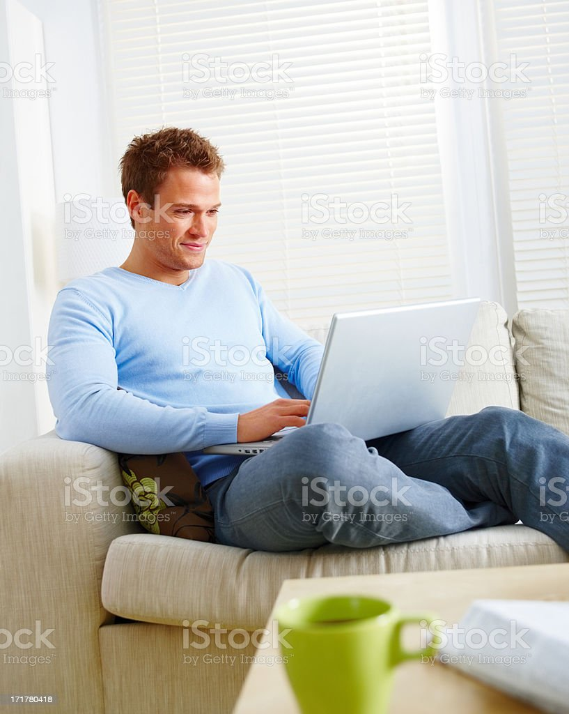 Young man working on laptop computer in living room stock photo