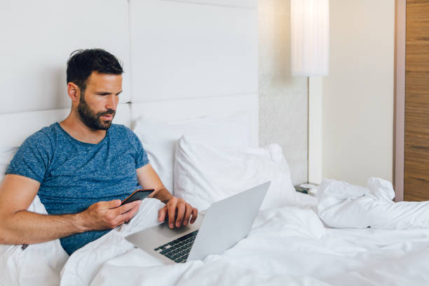 Young man working on laptop in bed stock photo