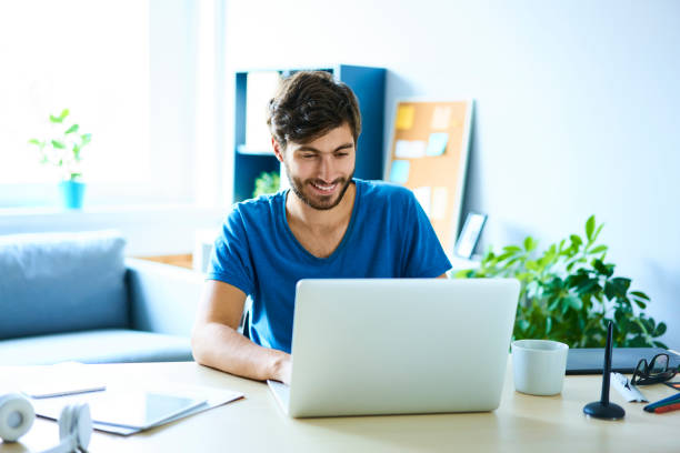 Young man working on laptop in home office and smiling stock photo