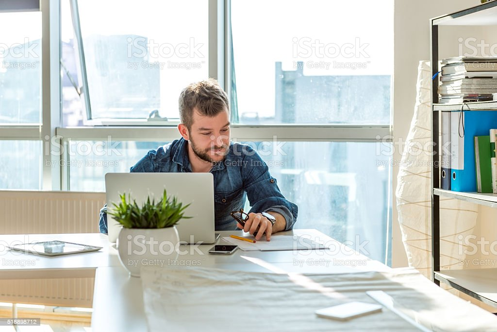 Young man working on laptop stock photo