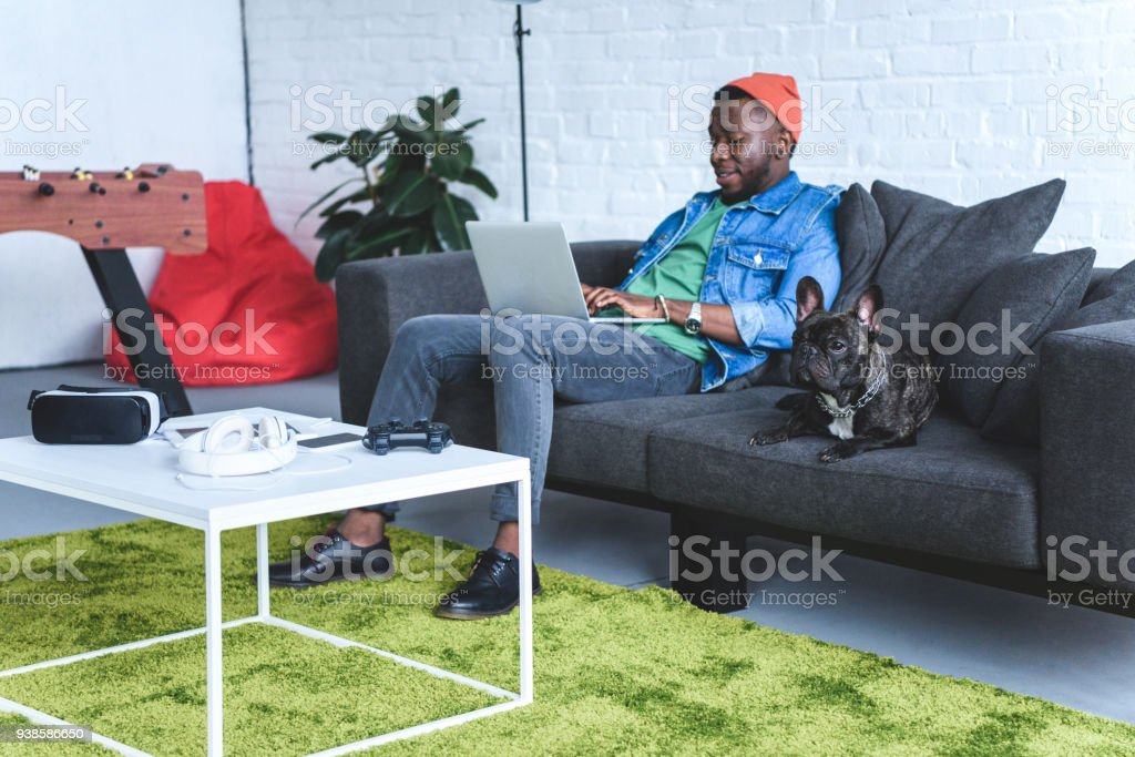 Young man working on laptop while sitting on sofa with bulldog and digital gadgets on table stock photo