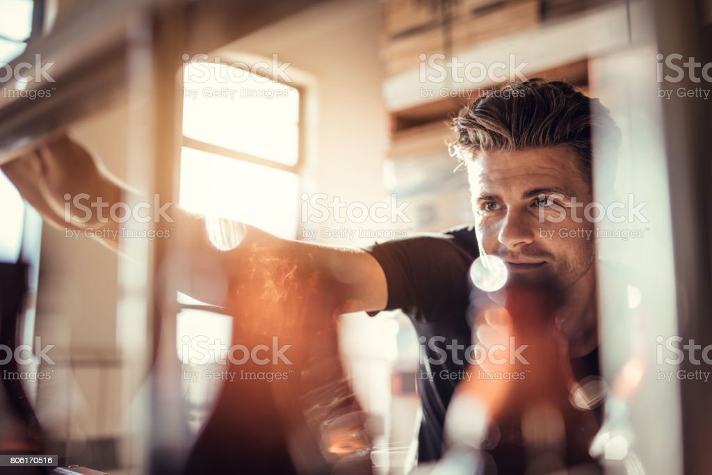 Young man working on the beer bottling machine stock photo