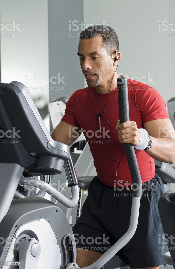 Young man working out on an elliptical royalty-free stock photo