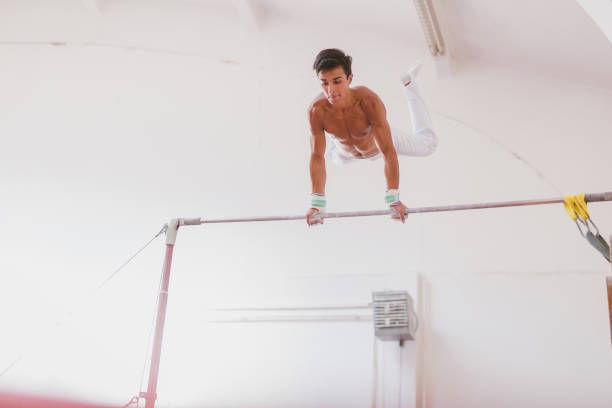 young man working out on horizontal bar - horizontal bar stock photos and pictures