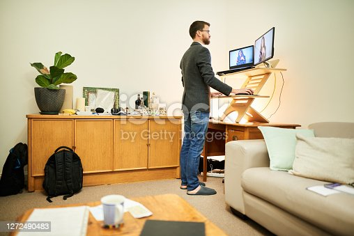 istock Young man working remotely at a standing desk in his living room 1272490483