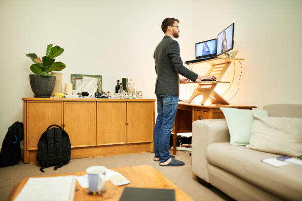 Young man working remotely at a standing desk in his living room stock photo