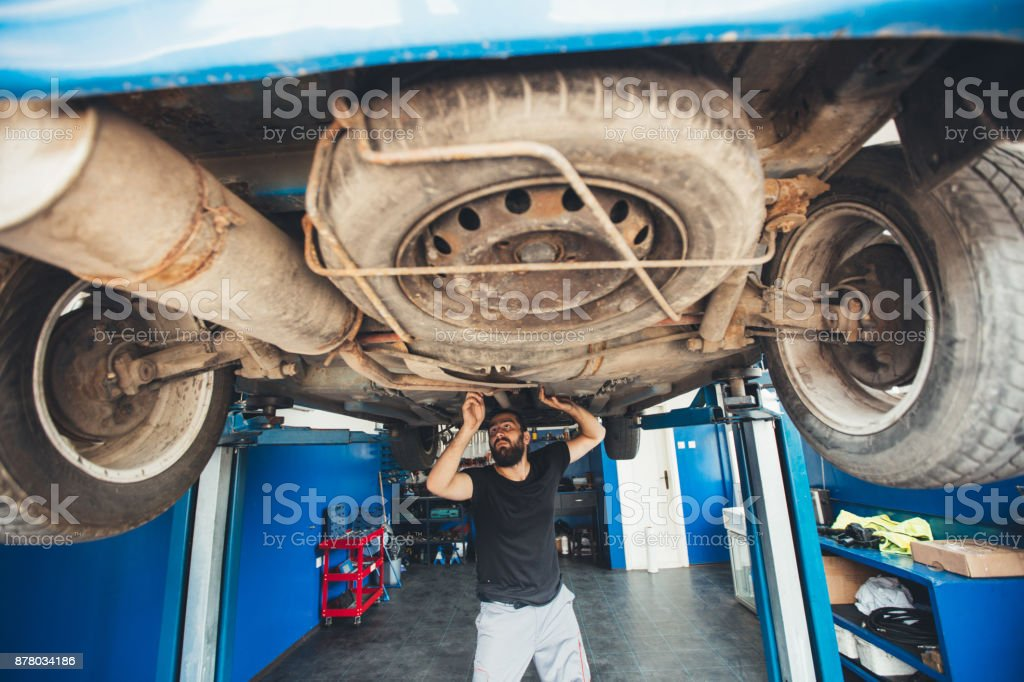 Young man working under a vehicle stock photo