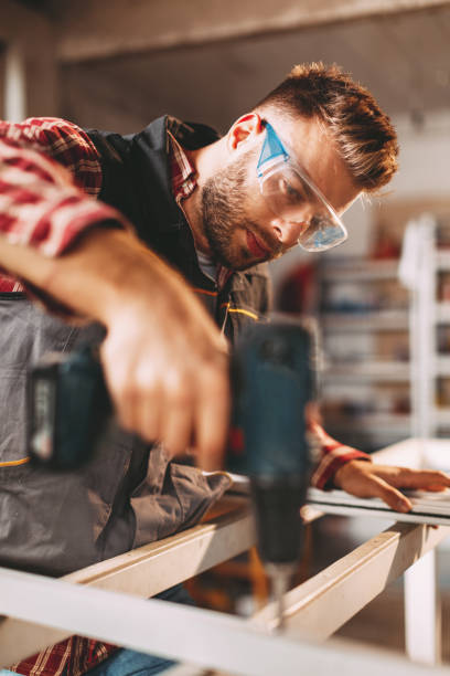 Young man working with drill in the workshop stock photo