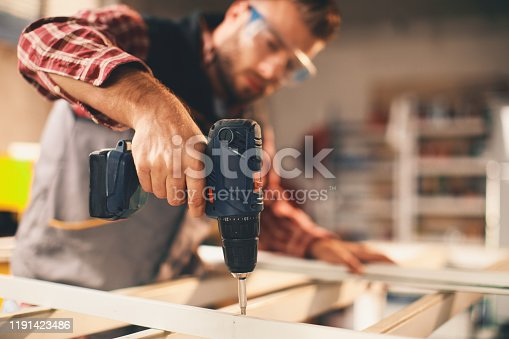 Young man working with drill in the workshop