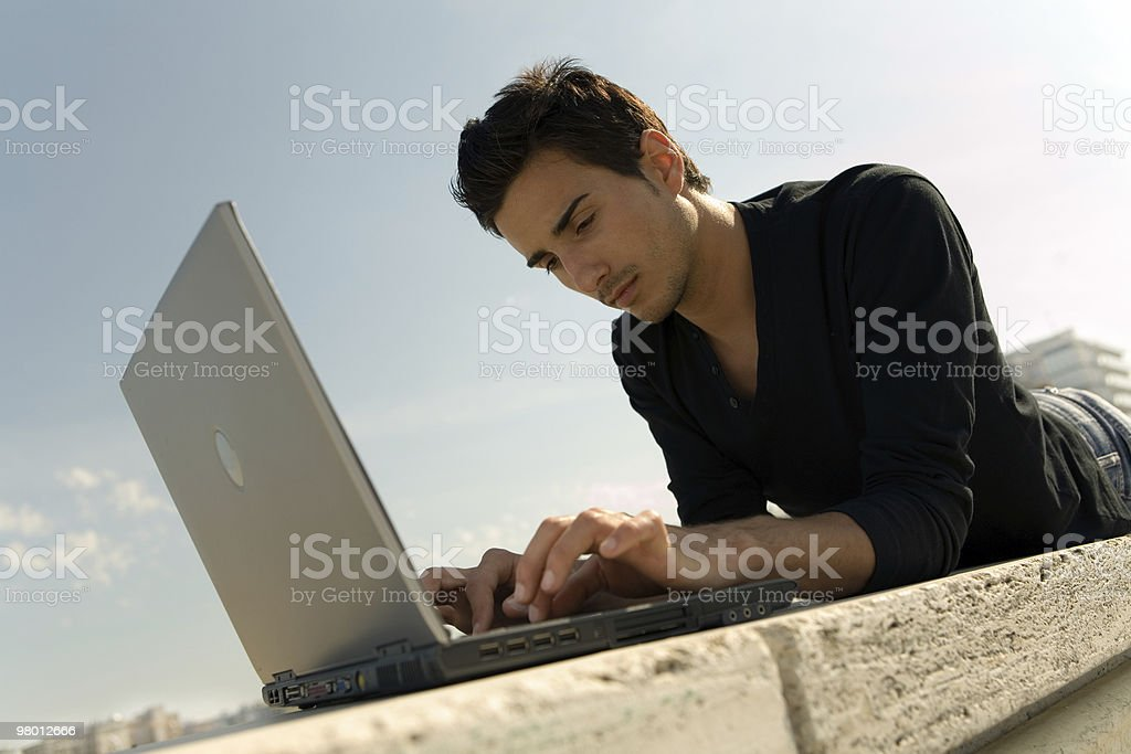 Young man working with laptop outdoor royalty-free stock photo