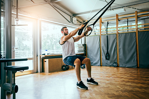 istock Young man workout with TRX Suspension 1042684380