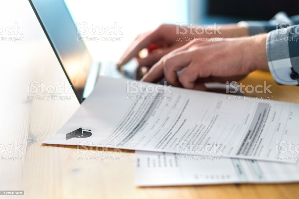 Young man writing college or university application form with laptop. Student applying to school. Scholarship document, admission paper or letter on table. Typing email. stock photo