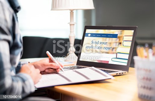 Young man writing college or university application form with pen and paper. Student applying or filling document. Scholarship, grant or admission. School website in laptop.