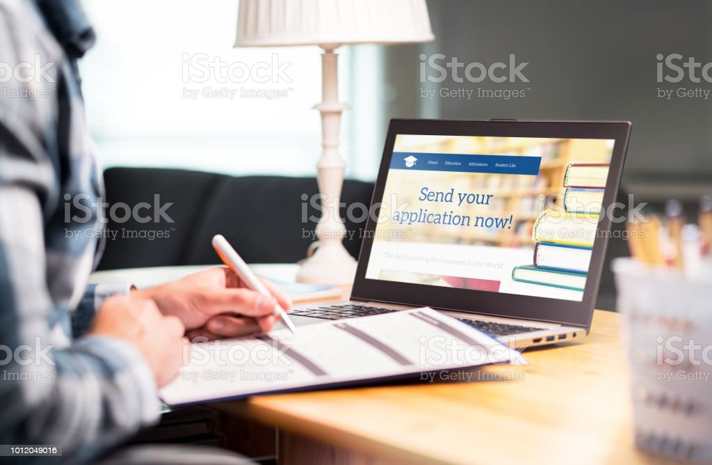 Young man writing college or university application form with pen and paper. Student applying or filling document. Scholarship, grant or admission. stock photo