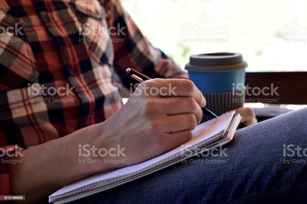 young man writing in a notebook stock photo