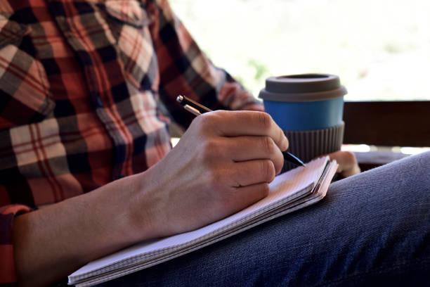 junger mann schreiben in notebook - drehbuchautor stock-fotos und bilder