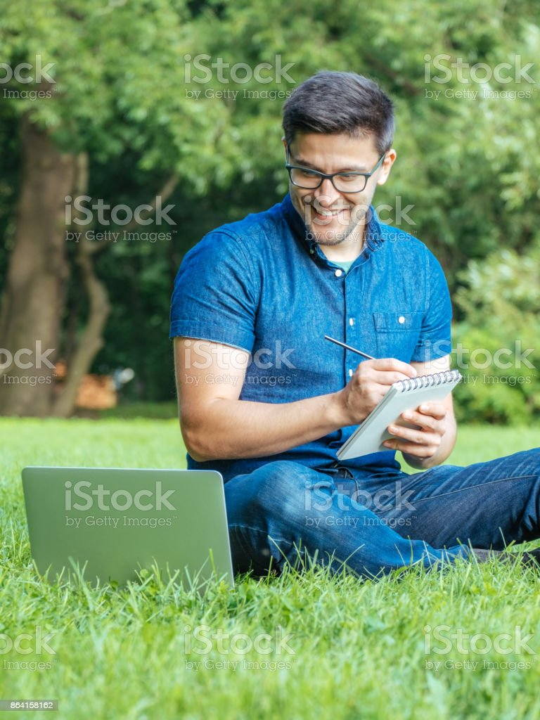 Young man writing in his sketchbook in city park. Idea, inspiration concept royalty-free stock photo