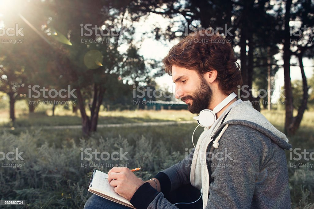 Young man writing in notebook at nature, side view stock photo