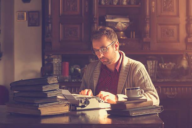 Jovem escrevendo na velha máquina de escrever. - foto de acervo