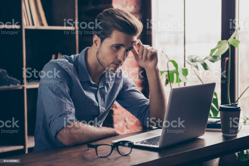 Young manager in checkered shirt reading information on the Internet on his computer royalty-free stock photo