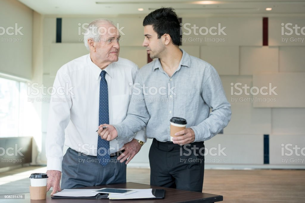 Young Manager Offering his Idea to Skeptical Boss Young manager offering pen to upset senior employee for signing document. Business owner firing senior executive. Employee pushing his idea to skeptical boss. Business and communication concept. Adult Stock Photo