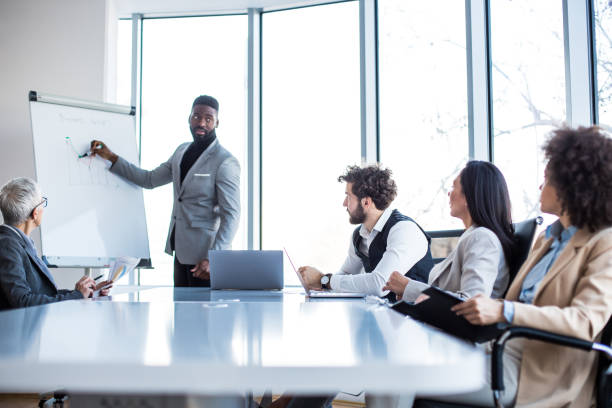 A young manager presenting the graph results on the whiteboard to the board at the conference room. stock photo