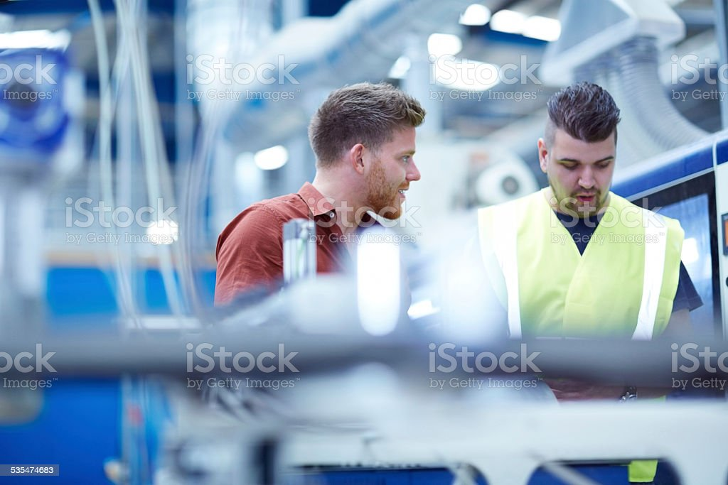 Young manager with foreman on factory shopfloor stock photo