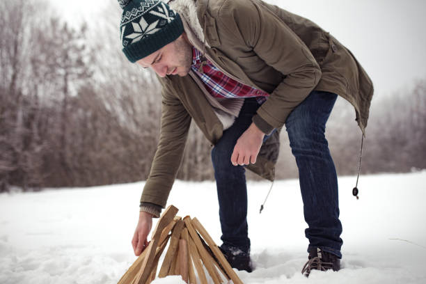 Young manreparing wood for a campfire stock photo