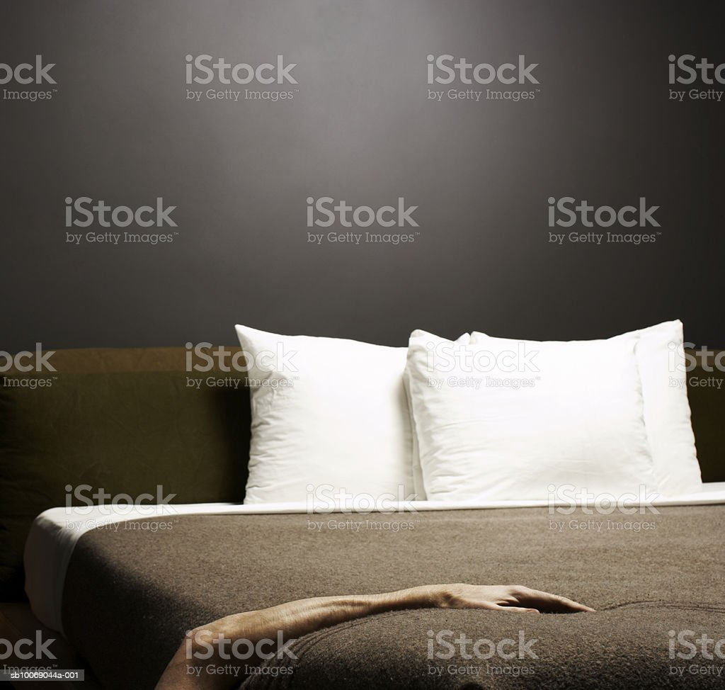 Young man's hand on bed royalty-free stock photo
