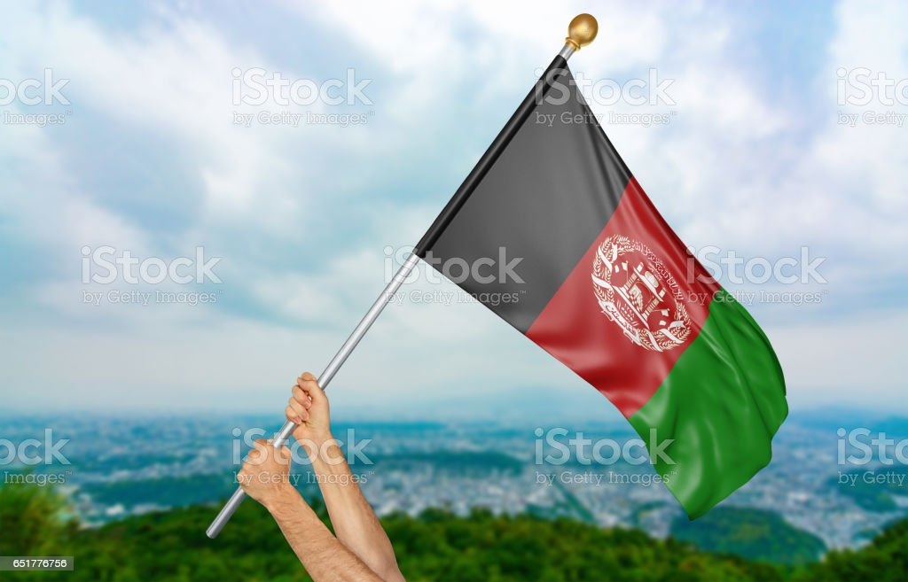 Young man's hands proudly waving the Afghanistan national flag stock photo