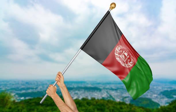 Mãos do jovem acenando orgulhosamente a bandeira nacional do Afeganistão - foto de acervo