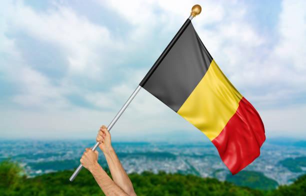 junger mann hände stolz schwenkten die nationalflagge belgien - freistaat stock-fotos und bilder