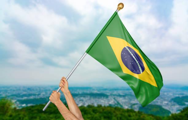 junger mann hände stolz schwenkten die nationalflagge brasilien - freistaat stock-fotos und bilder