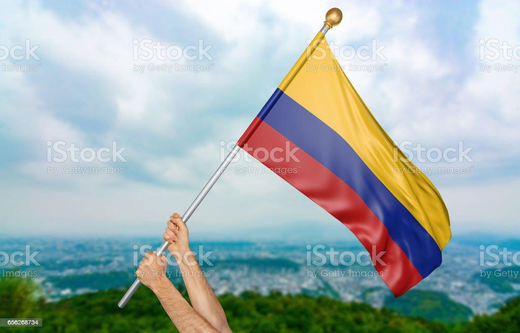Manos del joven orgullosamente ondeando la bandera nacional de Colombia - foto de stock
