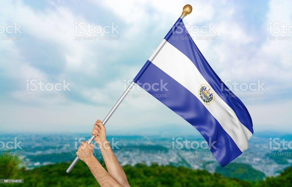 Manos del joven orgullosamente ondeando la bandera nacional del Salvador - foto de stock