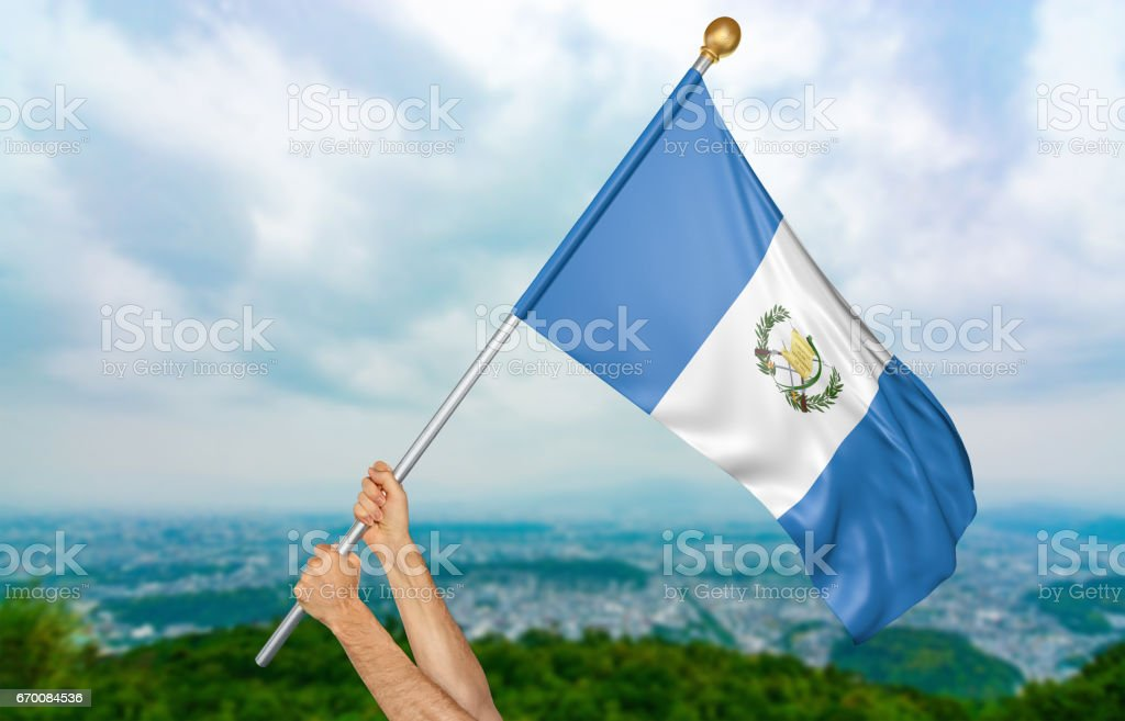 Young man's hands proudly waving the Guatemala national flag stock photo