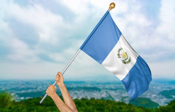 Manos del joven orgullosamente ondeando la bandera nacional de Guatemala - foto de stock