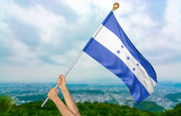 manos del joven orgullosamente ondeando la bandera nacional de honduras - bandera de honduras fotografías e imágenes de stock