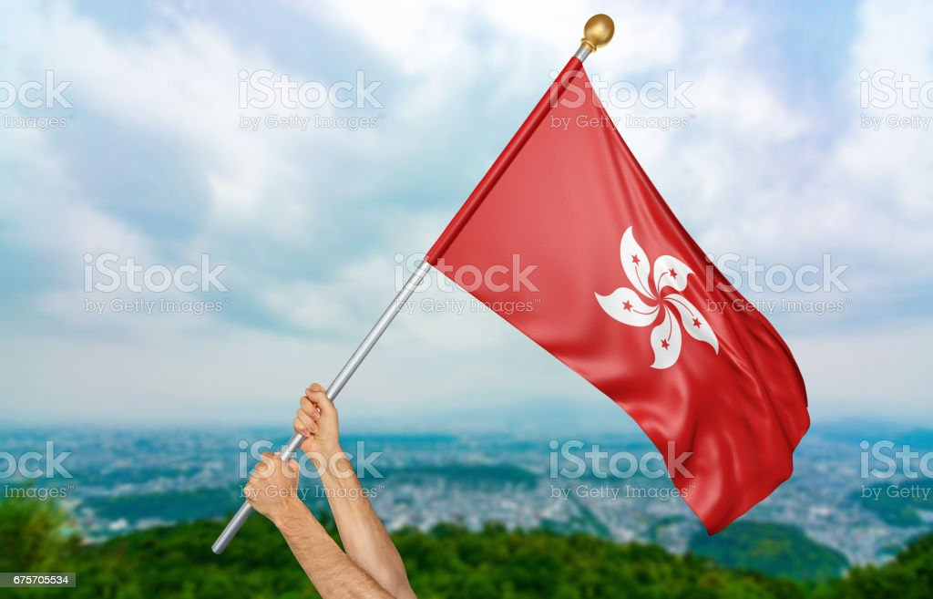Young man's hands proudly waving the Hong Kong national flag royalty-free stock photo