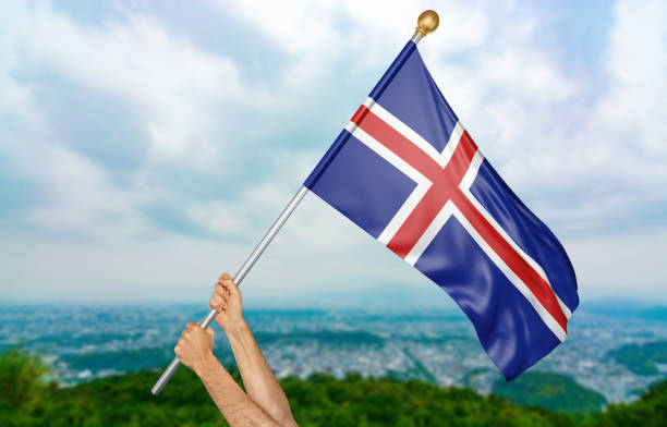Mãos do jovem acenando orgulhosamente a bandeira nacional da Islândia no céu - foto de acervo