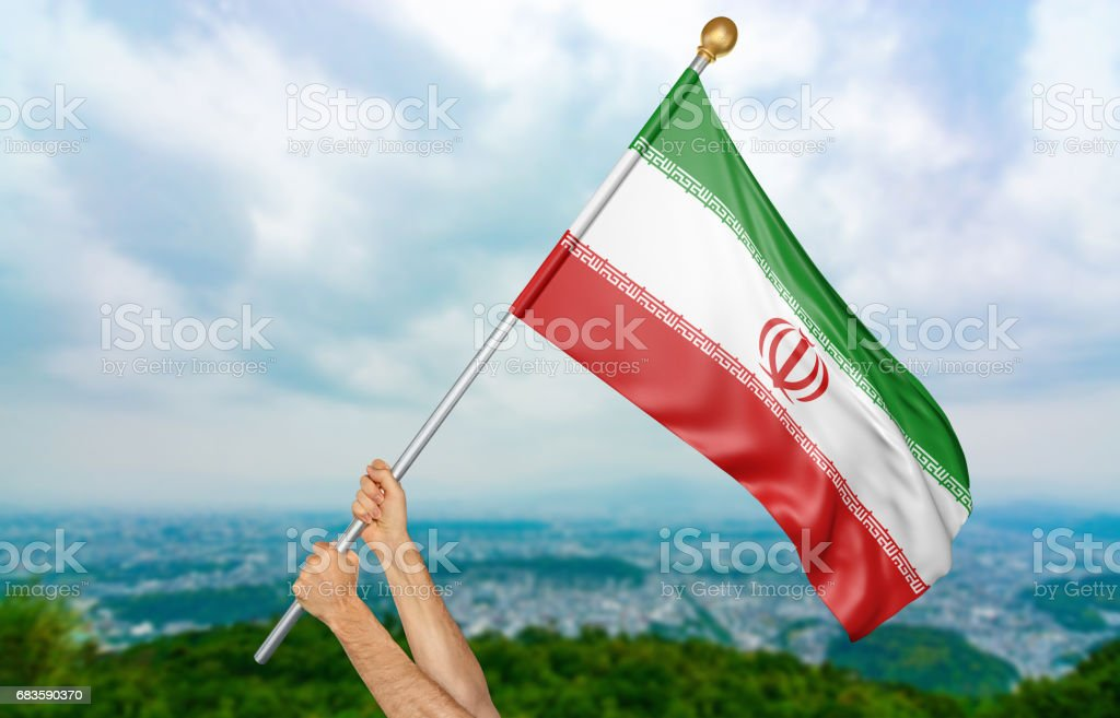 Young man's hands proudly waving the Iran national flag stock photo