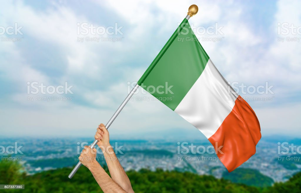 Young man's hands proudly waving the Ireland national flag in the sky stock photo
