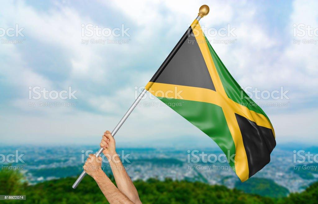 Mãos do jovem acenando orgulhosamente a bandeira nacional da Jamaica no céu - foto de acervo