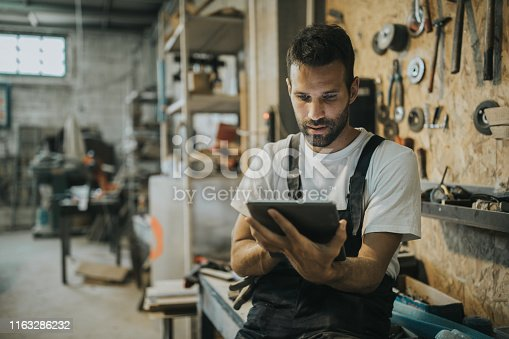 Young carpenter surfing the net on touchpad in a workshop.