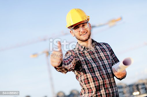 617878058 istock photo Young manual worker with yellow hemlet showing thumbs up 544488952